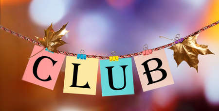 CLUB word on clothespins in front of defocused luminous lights