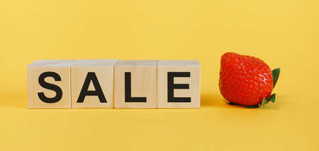 Word SALE made with wooden building blocks on a yellow background