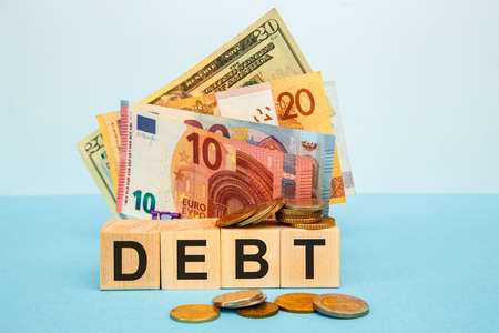 Wooden blocks with the word Debt. Reduction or restructuring of debt. Refusal to pay debts or loans and invalidate them