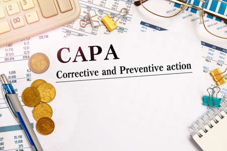 Paper with Corrective and Preventive action CAPA on the table, financial documents, calculator and coins Stok Fotoğraf