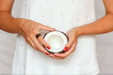 Hands of a young woman holding half a coconut. healthy eating concept