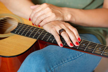 A girl's hand as she hold an acoustic guitar by the neck