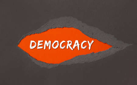 DEMOCRATY- the inscription appears behind the torn paper.