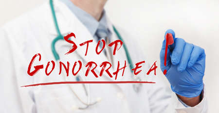 Doctor's hand writing with a marker Stop Gonorrhea. Medical concept