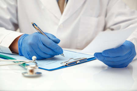A doctor in protective gloves writes out a prescription for medicines.
