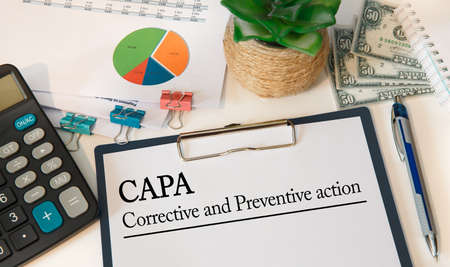 Paper with Corrective and Preventive action CAPA on the table, calculator and money