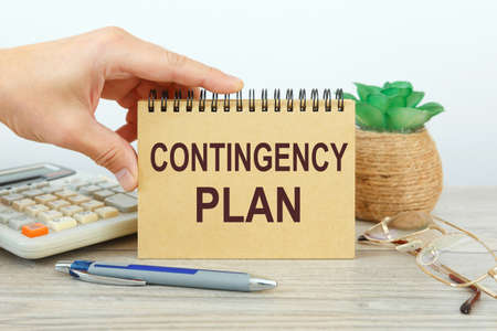 Notepad with text Contingency Plan on a white background, near calculator and office supplies. Business concept.