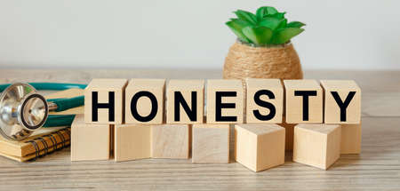 Wooden cubes with the abbreviation HONESTY and stethoscope