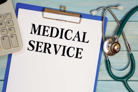 Worksheet with the inscription Medical Service, stethoscope and calculator. Medical concept. Reklamní fotografie