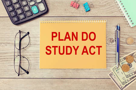 Notebook with the text PLAN DO STUDY ACT on the office table among the stationery. Business concept. Stock Photo
