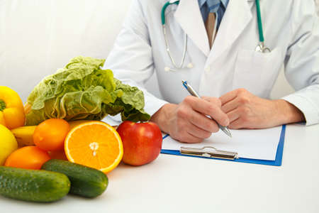 Nutritionist doctor writing diet plan on table. Right nutrition and slimming concept