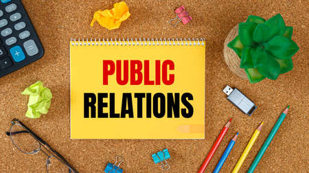 Public Relations is written on a notepad, on an office desk with office accessories.