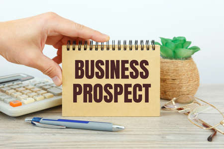 BUSINESS PROSPECT is written on a notepad on an office desk with office accessories.