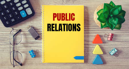 Public Relations is written in a notebook on an office table with office supplies.