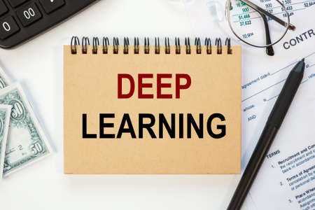 Deep learning is written in a notebook on an office table with office supplies.