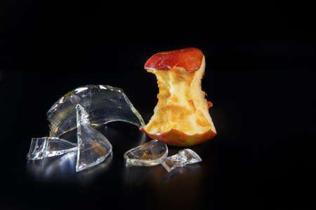 Apple core and shards of glass on a black background with reflection. Ecology and waste recycling concept.
