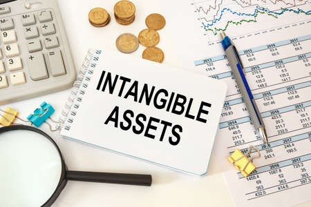 Intangible assets is written on a notepad on an office desk with office accessories.