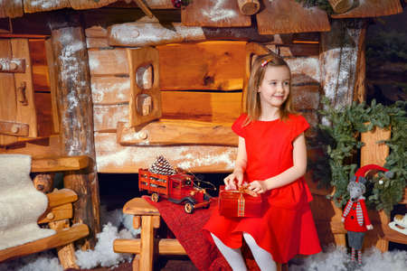Little girl in a red dress with a Christmas present near a fabulous house Zdjęcie Seryjne