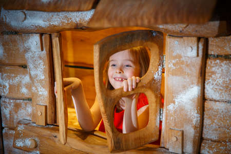 Little girl in a red dress opens the window of a fabulous house