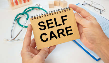 Notepad with text SELF CARE in the hands of a doctor and a stethoscope, medical concept.