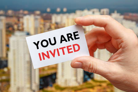 Male hand holds a card with the inscription You Are Invited on a sity background