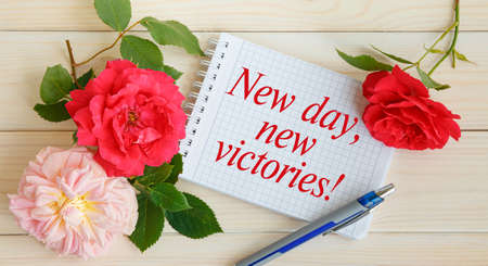Red roses and a notebook with the inscription New day, new victories. Motivation of a good mood. Stock Photo