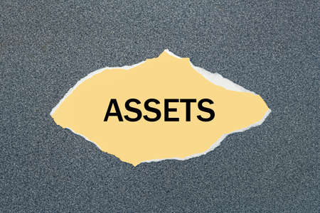 ASSETS - written on torn yellow paper. Gray background Banco de Imagens