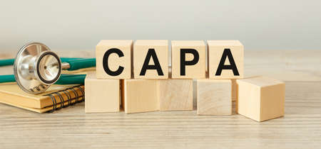 CAPA corrective and preventive action plan - inscription on wooden cubes