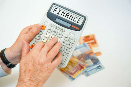 An elderly woman holds a calculator in her hands and calculates expenses. Financial concept