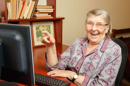 An elderly woman is studying the computer and watching the internet
