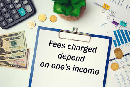 Paper with text - Fees charged depend on ones income - on the office table, calculator and money