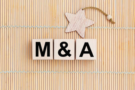 Wooden cubes with the abbreviation M and A - Merger and Acquisition