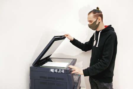 Young man in a protective mask makes copies of documents on a copy machine in the office