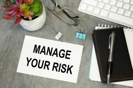 MANAGE YOUR RISK- lettering on paper on the desktop, notepad, pen and keyboard. Concept photo of the advantage. Stock Photo