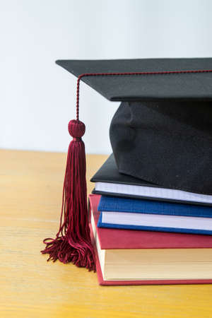 Closeup on black bonnet for graduation ceremony on top of books Stock Photo