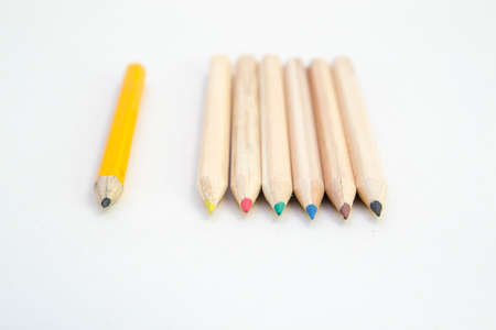 Six wood colored crayons on white background and a single grey one.