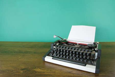 Vintage typewriter on wooden desk. Mint green background.