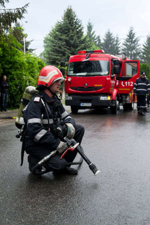 A firefighter ready for action with a red firetruck in background. Romanian national emergency drill.