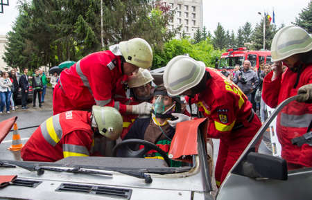 Firefighter rescuing wounded young man in car accident - Romanian National Emergency Exercise