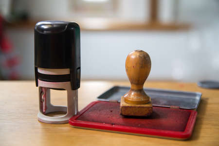 Automatic stamp and a wooden stamp on a red ink pad. Foto de archivo