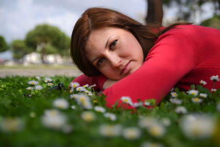 A portret of a young woman lying on green grass with white flowers.