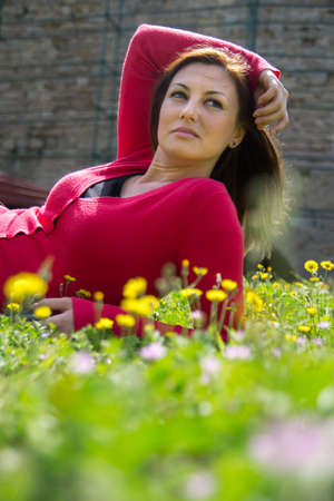 Portrait of a young woman lying on green grass with yellow flowers.