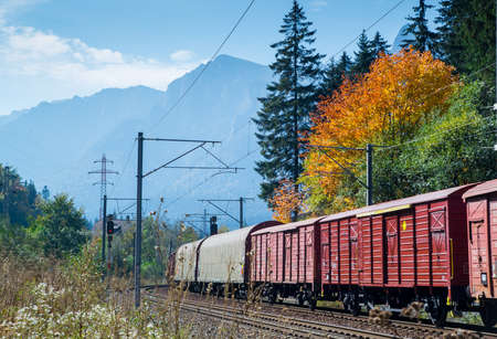 Cargo train with multiple wagons on railroad with autumn colors in the forest. Mountains and blue sky in the background. Editorial