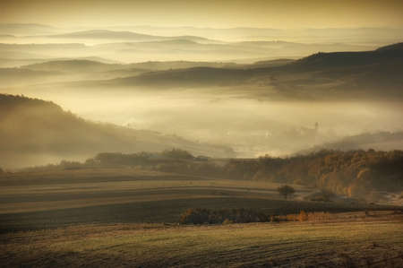 Landscape with haze and fog on a cold autumn morning over the hills photo