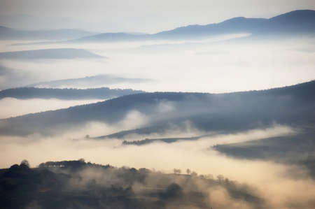 Fog above the mountains on a cold autumn morning with trees far away photo