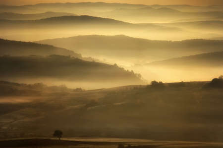 Morning landscape with fog over the hills in autumn