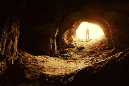 cueva: hombre de pie delante de una entrada de la cueva Foto de archivo
