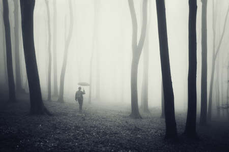 man with umbrella walking in a dark forest with fog and black trees with eerie atmosphere