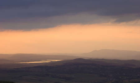 heavy storm clouds gathering over the hill near a lake at sunset photo