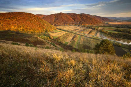 view of a valley over hills in autumn  photo